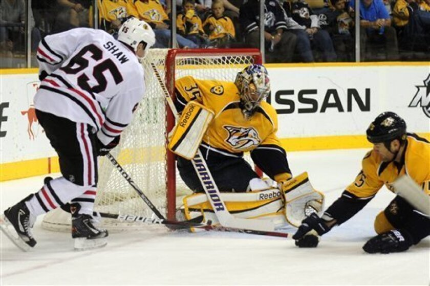 Chicago Blackhawks center Andrew Shaw (65) has his shot stopped by Nashville Predators goalie Pekka Rinne (35), of Finland, and Predators defenseman Hal Gill (75) in the first period of an NHL hockey game on Saturday, March 31, 2012, in Nashville, Tenn. (AP Photo/Mike Strasinger)