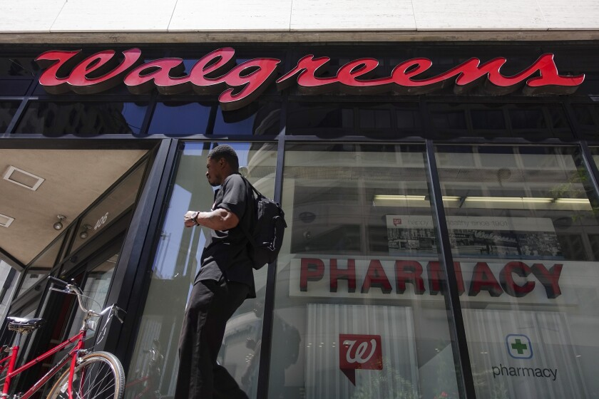 FILE - In this June 25, 2019, file photo signage hangs outside a Walgreens pharmacy in downtown Cincinnati. Walgreens reports financial results on Wednesday, Jan. 8, 2020. (AP Photo/John Minchillo, File)