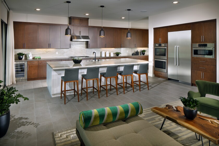 Gourmet kitchens in the Carmel neighborhood in Pacific Highlands Ranch flow into outdoor loggias, providing an ideal setting to entertain.