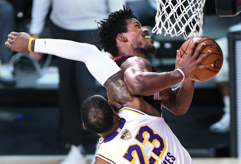 Lakers forward LeBron James fouls Miami forward Jimmy Butler.