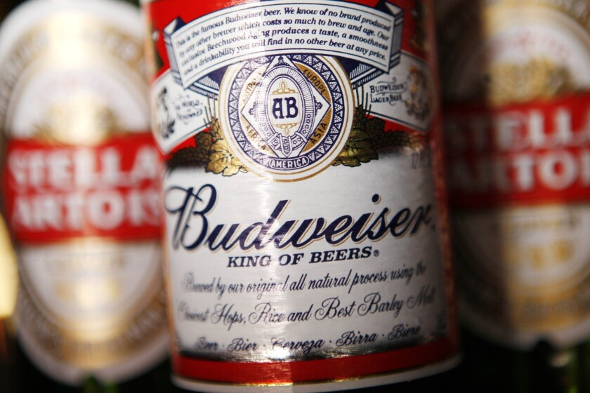 Bottles of Anheuser-Busch InBev beers Stella Artois and Budweiser. The company has announced that it will buy back a Korean brewery.