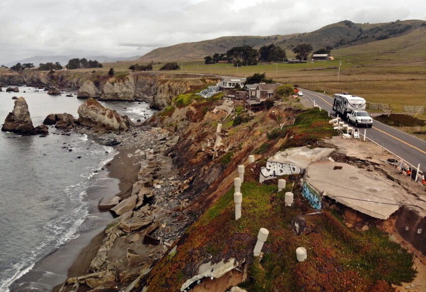 Crumbled concrete and seawalls on an eroding bluff between the ocean and a two-lane highway