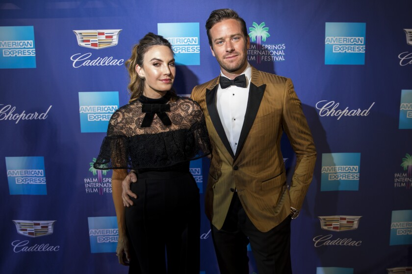 Elizabeth Chambers and Armie Hammer pose on a red carpet in 2018