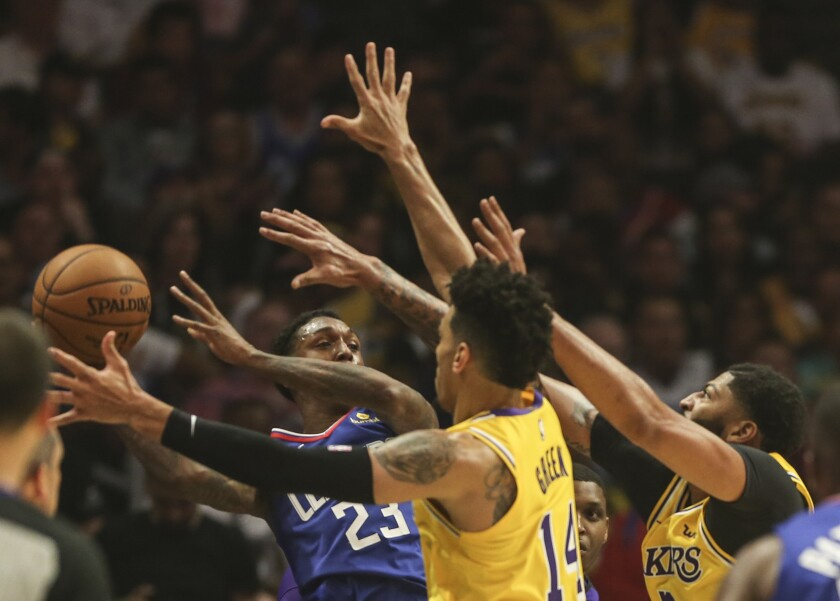Clippers guard Lou Williams looks to pass after he's trapped by Lakers defenders.