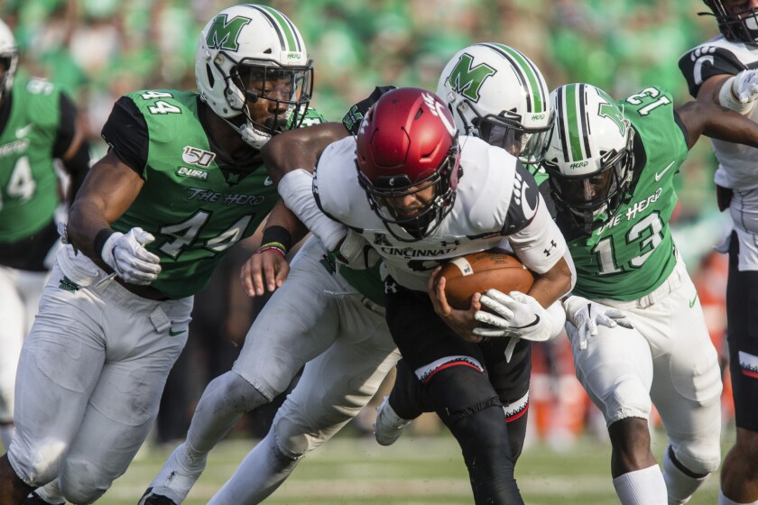 Marshall defenders swarm tackle Cincinnati quarterback Desmond Ridder an NCAA college football game on Saturday, Sept. 28, 2019, in Huntington, W.Va. (Sholten Singer/The Herald-Dispatch via AP)