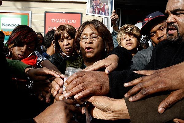 """Mary Alice Phillips leads a prayer at a vigil for her grandson, hip-hop artist Montae """"M-Bone"""" Talbert, who was killed in a drive-by shooting in Inglewood on Sunday night."""