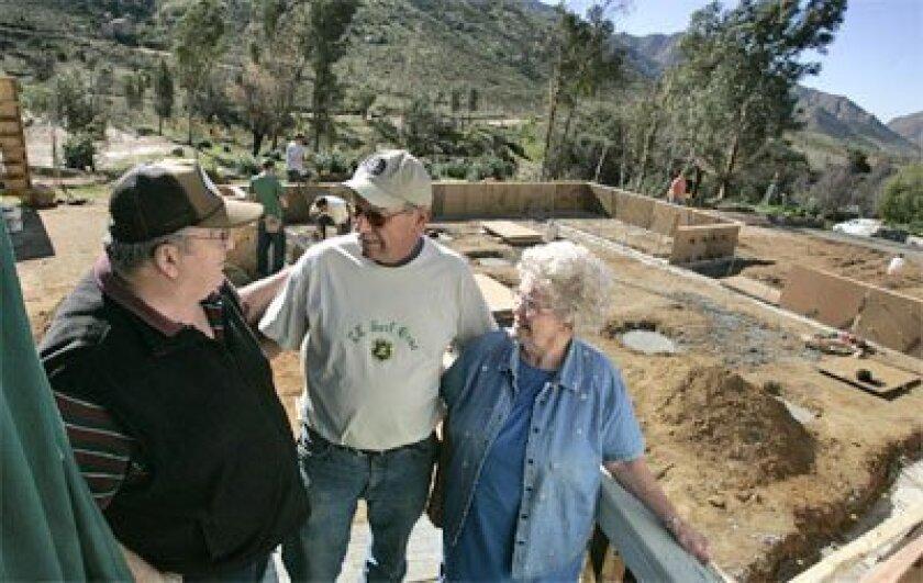 Steve and Elsie Campbell talked yesterday to Ernie Kornelsen (center), who is supervising the  volunteers rebuilding the Campbells' home in Barrett Junction. (John Gastaldo / Union-Tribune)