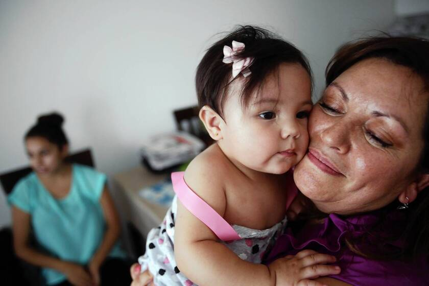 Susana Garcia snuggles with her granddaughter, 9-month-old Phia Garcia. With earnings of less than $13 an hour, she sees herself as part of the lower class.