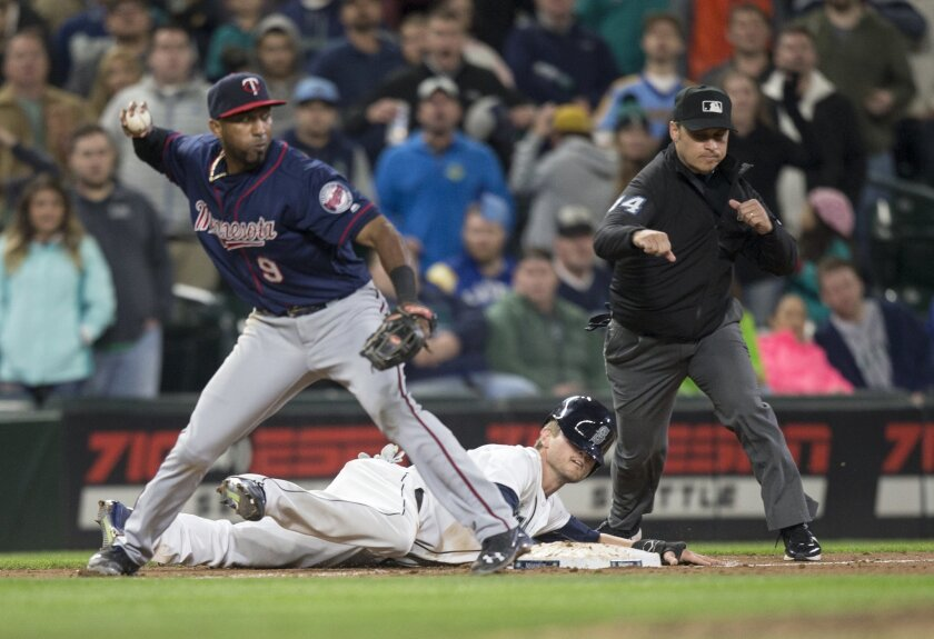 Seattle Mariners' Shawn O'Malley lays on the ground after being tagged out caught stealing by Minnesota Twins third baseman Eduardo Nunez who threw to second to complete a double play in the ninth inning of a baseball game, on Saturday, May 28, 2016, in Seattle. The Twins won 6-5. (AP Photo/Stephen Brashear)