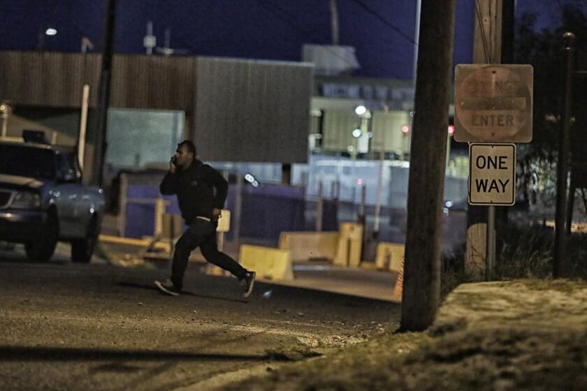 A border crosser hustles across Portscheller Street along Juarez Avenue in the shadow of the U.S. Customs border office in Roma, Texas.