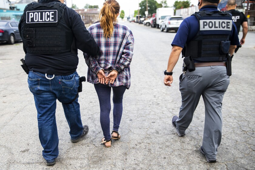 COMPTON, CALIF. - JUNE 10: Adriana Espejel is escorted away by Immigration and Customs Enforcement f