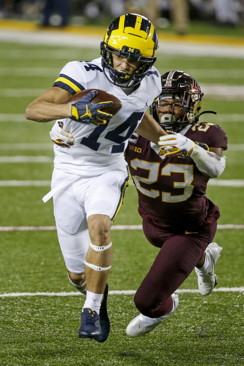 Minnesota defensive back Jordan Howden (23) tackles Michigan wide receiver Roman Wilson (14) on a pass play in the third quarter of an NCAA college football game Saturday, Oct. 24, 2020, in Minneapolis. Michigan won 49-24. (AP Photo/Bruce Kluckhohn)