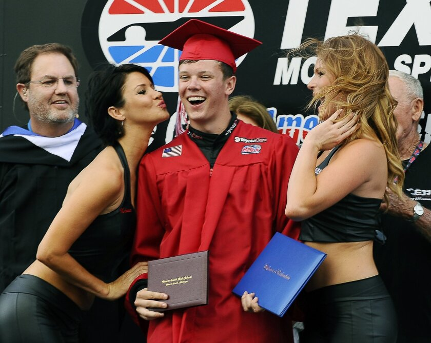 Erik Jones, center, takes part in a graduation ceremony on the stage during driver introductions for a NASCAR truck race at Texas Motor Speedway in Fort Worth, Texas, Friday, June 6, 2014. Tonight's race falls on the same day as Jone's high school senior graduation however, he chose to forego the opportunity to walk across the stage with his fellow classmates to drive in the race. (AP Photo/Ralph Lauer)