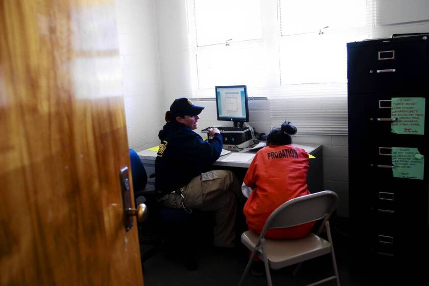 A probation officer helps a new arrival fill out paperwork at Camp Scudder, a locked facility in Santa Clarita run by the L.A. County Probation Department. The camp is testing a new screening program to address the health problems girls might face coming into the county's juvenile justice system and identify those who need help.
