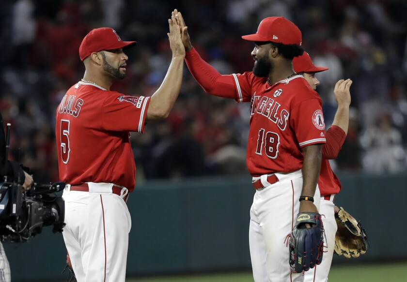 Angels' Albert Pujols, left, and Brian Goodwin celebrate after a 7-2 win over the Houston Astros.
