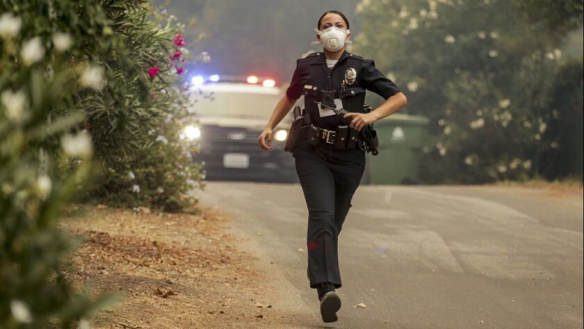 A police officer runs to evacuate residents in the La Tuna fire in Sunland, Calif. on Sept. 30, 2017.