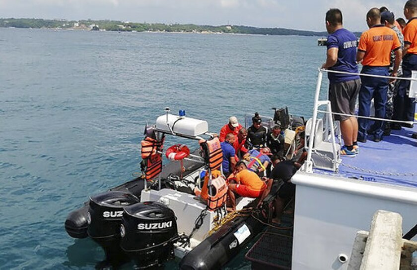 In this photo provided by Philippine Coast Guard in Manila, coast guard personnel carry a survivor to a waiting ambulance after being rescued from a capsized dragon paddle boat off Boracay island resort Wednesday, Sept. 25, 2019, in the central Philippines. The coast guard says seven rowers drowned and 14 others were rescued when their dragon boat was suddenly lashed by strong waves and overturned in the central Philippines. (Philippine Coast Guard Via AP)