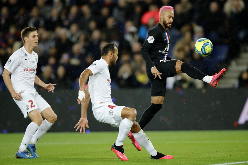 PSG's Neymar, right, controls the ball by Montpellier's Vitorino Hilton, center, and Arnaud Souquet during the French League One soccer match between Paris-Saint-Germain and Montpellier at the Parc des Princes stadium in Paris, Saturday Feb. 1, 2020. (AP Photo/Christophe Ena)