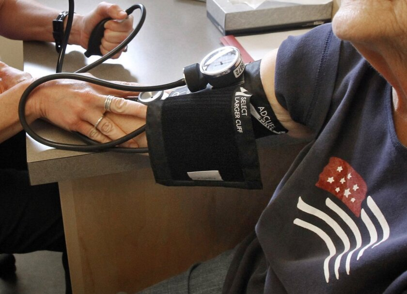 A patient has her blood pressure checked by a registered nurse in Plainfield, Vt. A major new U.S. study shows that treating high blood pressure more aggressively than usual cuts the risk of heart disease and death in people over age 50, the National Institutes of Health said Friday.