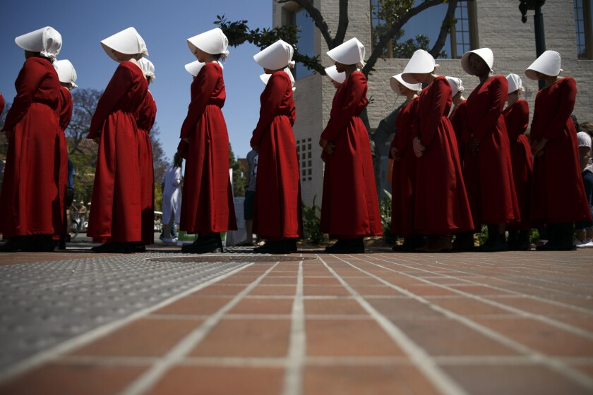 "Hulu's adaptation of ""The Handmaid's Tale"" sent actresses to the Festival of Books on Sunday for som"