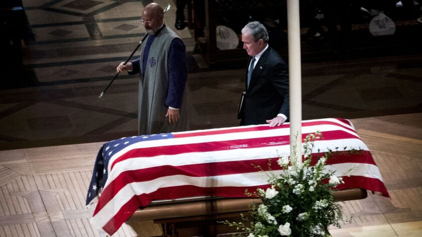 Former President George W. Bush touches the coffin as he arrives to deliver the eulogy during the funeral of his father, former President George H.W. Bush, at the National Cathedral in Washington on