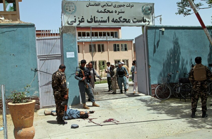 EDS NOTE: GRAPHIC CONTENT -- Afghan security forces stand guard at the gate of Ghazni's court building as a body, identified by police as that of a policeman, lies on the ground, after a deadly Taliban attack, in Ghazni, Afghanistan, Wednesday, June 1, 2016. The Afghan Interior Ministry said that T
