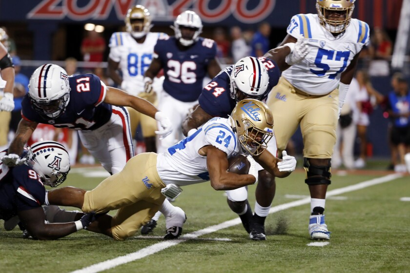 UCLA running back Zach Charbonnet (24) is brought down during the first half of the team's NCAA college football game against Arizona on Saturday, Oct. 9, 2021, in Tucson, Ariz. (AP Photo/Chris Coduto)