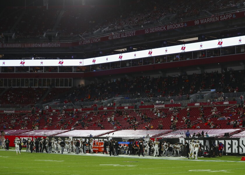 A limited number of fans sit inside Raymond James Stadium for a game between the Saints and Buccaneers.