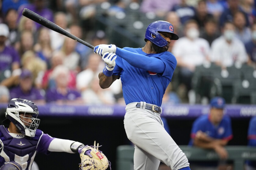 Chicago Cubs' Jason Heyward, right, grounds out to drive in a run against Colorado Rockies starting pitcher Kyle Freeland in the second inning of a baseball game Tuesday, Aug. 3, 2021, in Denver. (AP Photo/David Zalubowski)