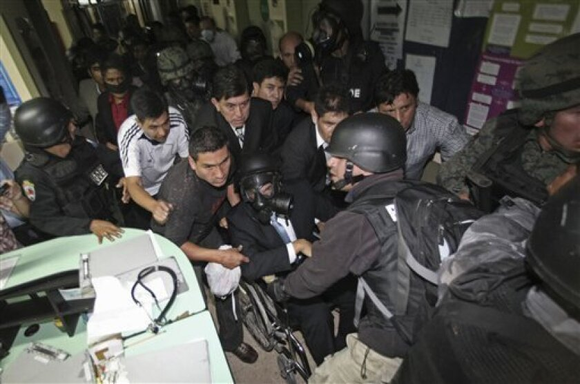 Ecuador's President Rafael Correa, sitting in a wheelchair and wearing a gas mask, is rescued from a hospital where he was holed up by protesting police in Quito, Ecuador, Thursday Sept. 30, 2010. The army rescued Correa from a hospital where he had been trapped by rebellious police for more than 12 hours while he was being treated for tear-gas fired by hundreds of police angry over a law that they claim would cut their benefits. (AP Photo/Dolores Ochoa)
