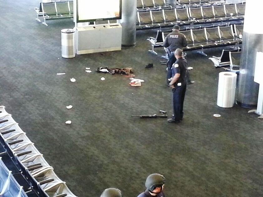 Police officers stand near an assault-style rifle in Terminal 3 of Los Angeles International Airport where a gunman opened fire on Nov. 1, killing one person and wounding three others.