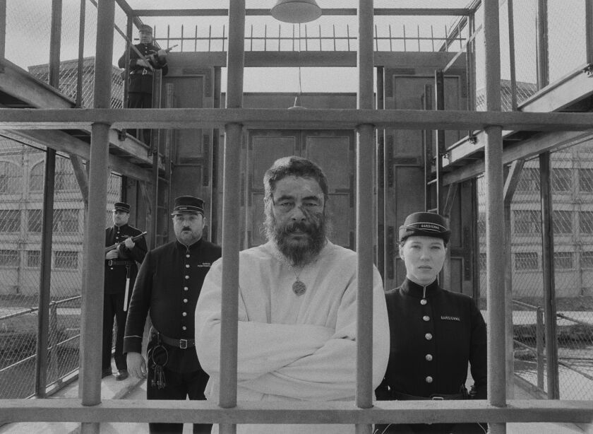 A male guard and a female guard flank a straitjacketed prisoner staring out through prison bars.