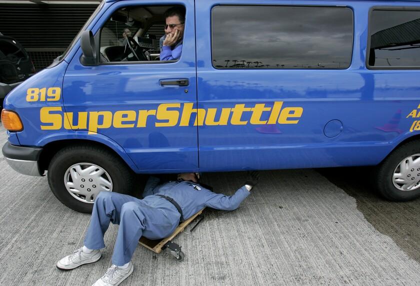 CHP motor carrier specialist Jerry Klein inspects the underbody of Vrej Tachjian's Super Shuttle van.