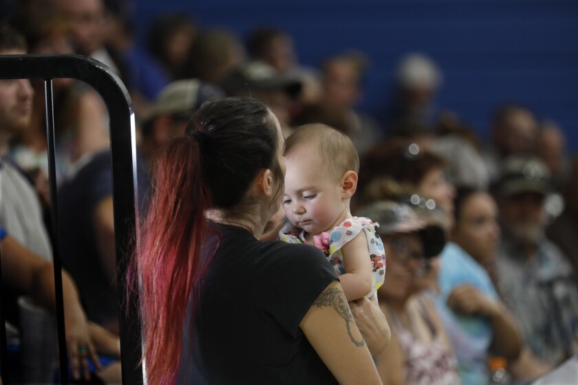 Trona resident Casey Huggins holds her friend's baby, Allison Jordan, during Wednesday's town hall meeting. Huggins' home is no longer habitable after twin earthquakes rocked the area last week.