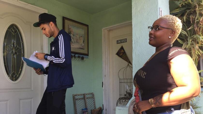 Wendell Sherman (izquierda), de Long Beach, y Amber-Rose Howard, de las organizaciones All of Us or None y A New Way of Life, hacen campaña el 5 de noviembre pasado, en Long Beach. Sherman se enfocó en las proposiciones 55, 56 y 57 (Robin Abcarian/Los Angeles Times).