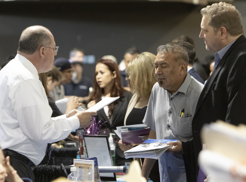 Job applicants talk to employers during a job fair at the Murrieta Spectrum with dozens of local employers last year.