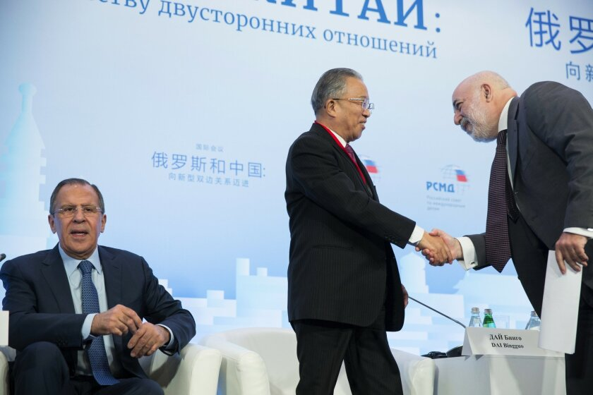 Chairman of the Chinese Chapter of the Russian-Chinese Committee of Friendship, Peace and Development Dai Bingguo, center, shakes hands with Russian businessman Viktor Vekselberg, as Russian Foreign Minister Sergey Lavrov, left, attends the Russian International Affairs Council in Moscow, Russia, T