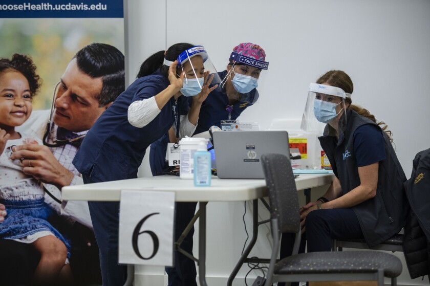 UC Davis Medical Center nurses, from left, Analyn Corpuz, Raenne Takara and Heather Donaldson review the process of inoculating with the Pfizer-BioNTech COVID-19 vaccine, Tuesday, Dec. 15, 2020 in Sacramento, Calif. (AP Photo/Hector Amezcua, Pool)