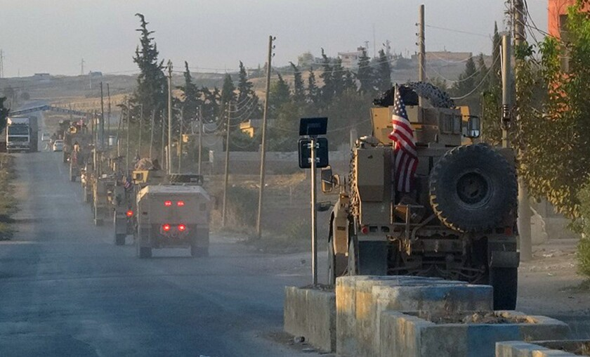 U.S. military vehicles travel a main road in northeastern Syria on Oct. 7, 2019, the day after President Trump announced a U.S. troop withdrawal in the area.