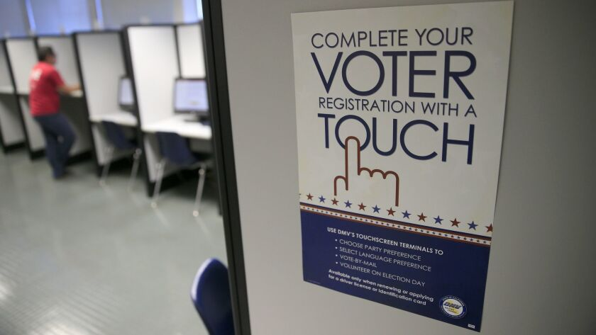 A sign advertises a touch-screen machine, a new process for voter registration at the Department of Motor Vehicles in Santa Ana.