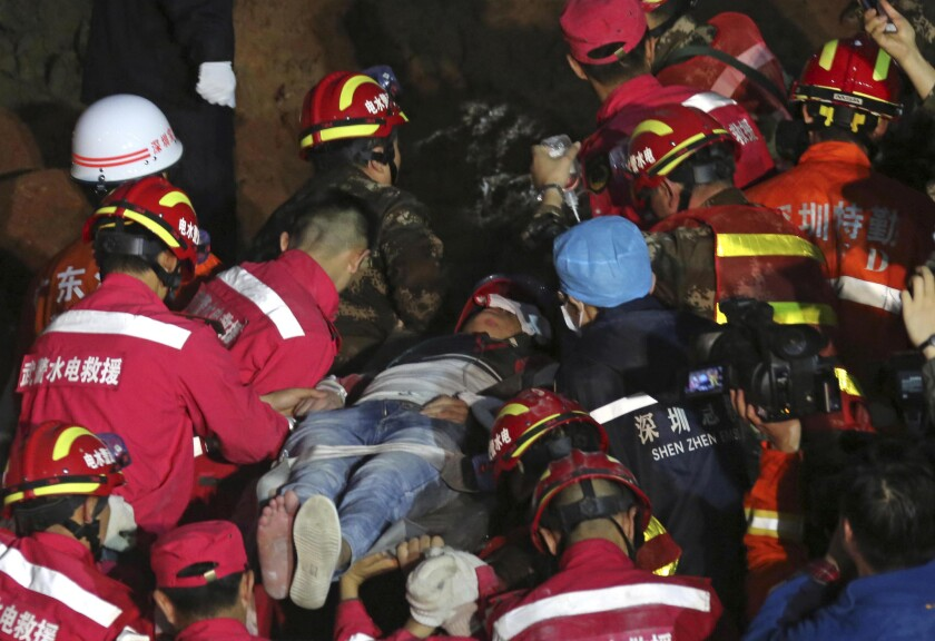 A survivor is transported on Dec. 23 from the site of a landslide in Shenzhen, China.