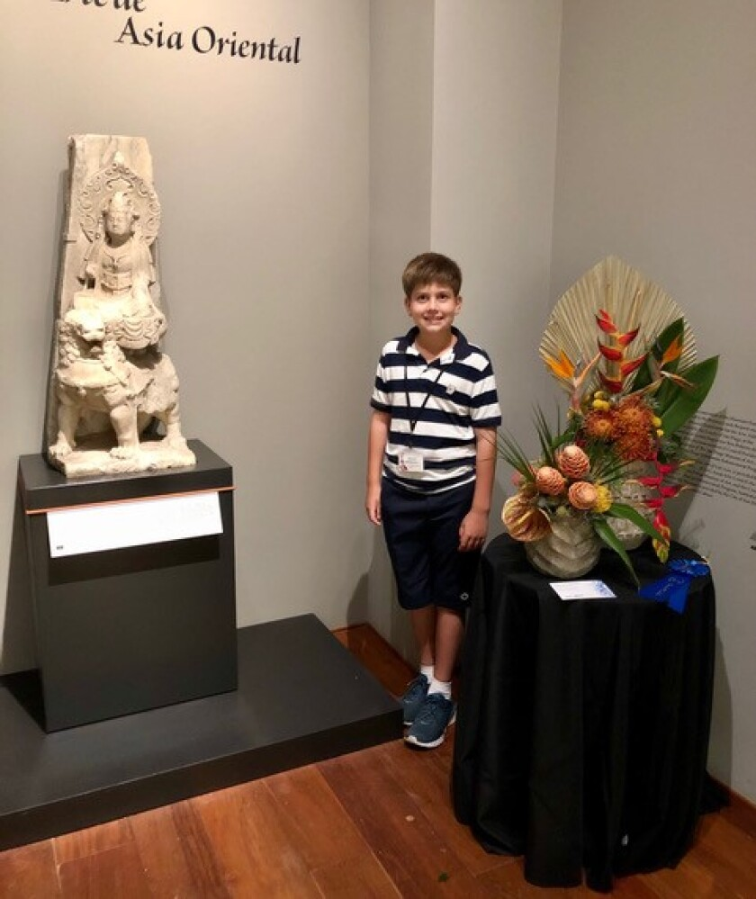 Marcel Halldorson poses with his award-winning floral arrangement for Art Alive and the sculpture he used for inspiration.