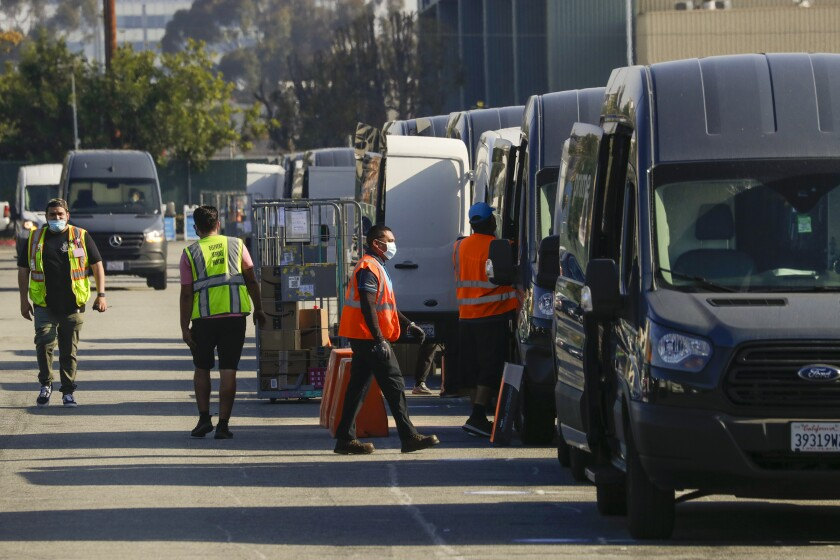 Packages are loaded in delivery vans at an Amazon warehouse facility in Hawthorne.