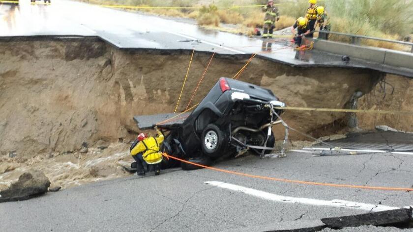En esta imagen proporcionada por el departamento de bomberos del condado de Riverside, equipos de emergencia trabajan después de que una camioneta quedara atrapada en el derrumbe de un tramo elevado de la Interestatal 10, el domingo 19 de julio de 2015, en Desert Center, California. (Jefe Geoff Pemberton/CAL FIRE/Bomberos del condado de Riverside via AP) ATRIBUCION OBLIGATORIA