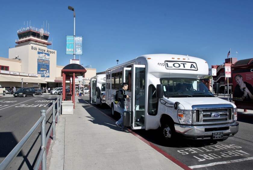 An airport shuttle picks up a passenger headed to Lot A from the Bob Hope Airport in Burbank on Tuesday, November 17, 2015. On Monday, airport officials inaugurated the airport's new fleet of 13 compressed-natural-gas shuttle buses with a ride on one of the vehicles, each of which seats 14 passengers and can accommodate two wheelchairs.