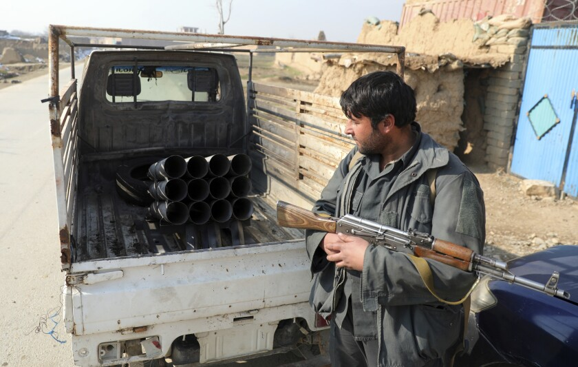 FILE - In this Dec. 19, 2020, file photo, an Afghan security official stands near a vehicle in which rockets were placed, in Bagram, north of Kabul, Afghanistan, Saturday, Dec. 19, 2020, after five rockets were fired at a major U.S. base in Afghanistan. The U.S. military has met its goal of reducing the number of troops in Afghanistan to about 2,500 by Friday, a drawdown that appears to violate a last-minute congressional prohibition. (AP Photo/Rahmat Gul, File)