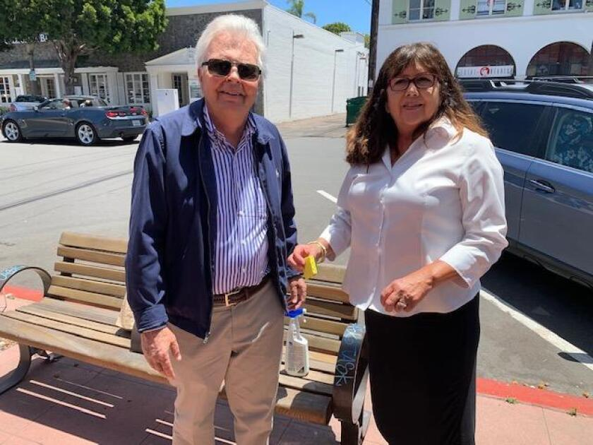 Local attorney Richard Circuit, and legal administer Nora Carver clean off graffiti on the benches in front of some stores on Girard Avenue and Prospect Street in the Village of La Jolla.