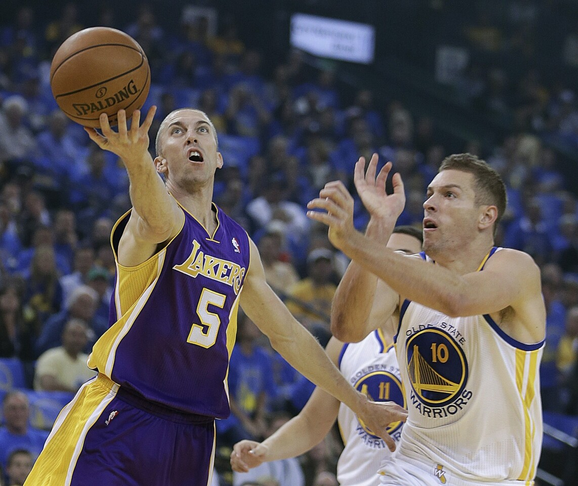 Lakers point guard Steve Blake gets past Warriors power forward David Lee for a layup in the 125-94 loss at Golden State on Wednesday night.