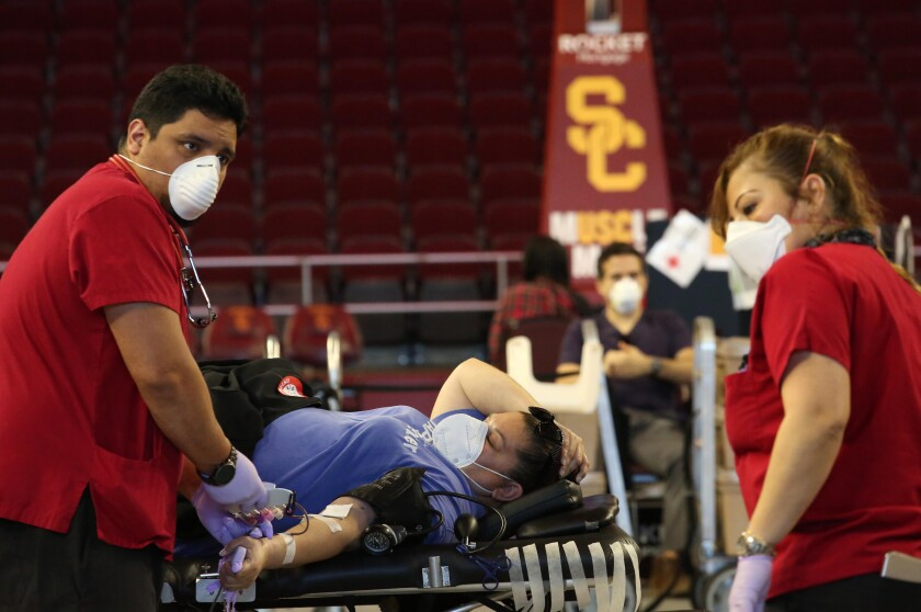 Red Cross technician Eddie Valdivia, left, and nurse Mercy Pineda work with a donor as USC Athletics and the Red Cross host a blood drive.