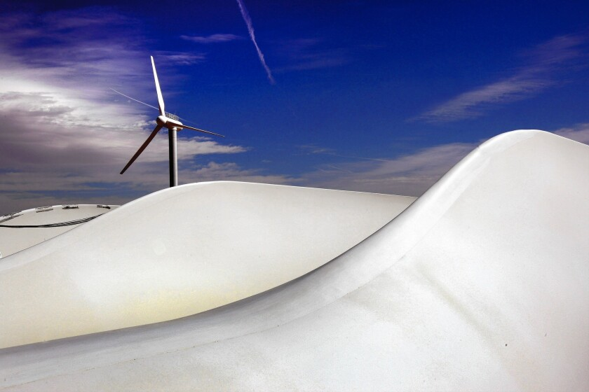 A wind turbine turns as giant turbine blades lie awaiting new construction at the National Renewable Energy Laboratory in Colorado in March 2009.